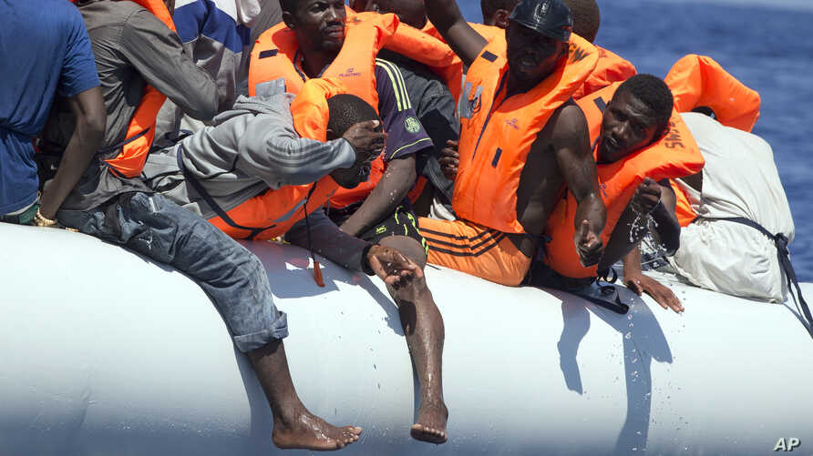 FILE - Migrants wearing life vests float in an inflatable boat during a rescue operation from the Aquarius vessel of SOS Mediterranee NGO and MSF (Doctors Without Borders) in the sea some 25 Nautical miles (29 miles, 46 kilometers) north of the Libya