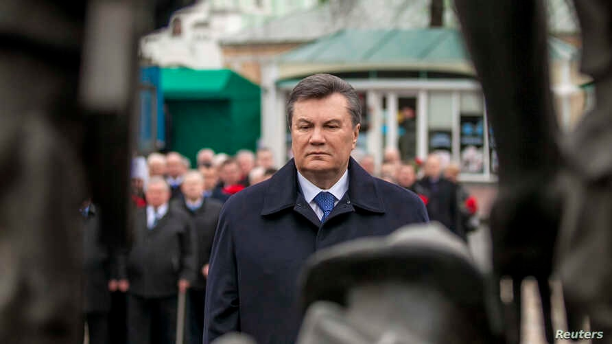 Ukraine's President Viktor Yanukovich takes part in a flower-laying ceremony at the memorial complex for Soviet Ukrainian-born victims of a military conflict in Afghanistan, Kiev, Feb. 14, 2014.