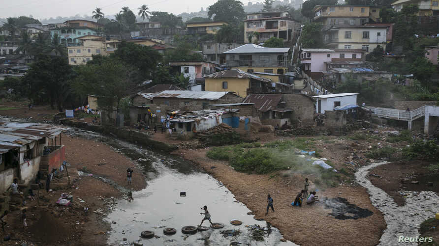 FILE - Kids jump on tires over a sewage in a slum in Freetown, Sierra Leone.