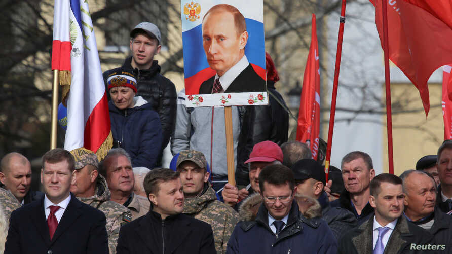 A man holds a board with a portrait of Russian President Vladimir Putin during celebrations of the fifth anniversary of Russia's annexation of Crimea in Simferopol, Crimea, March 15, 2019.