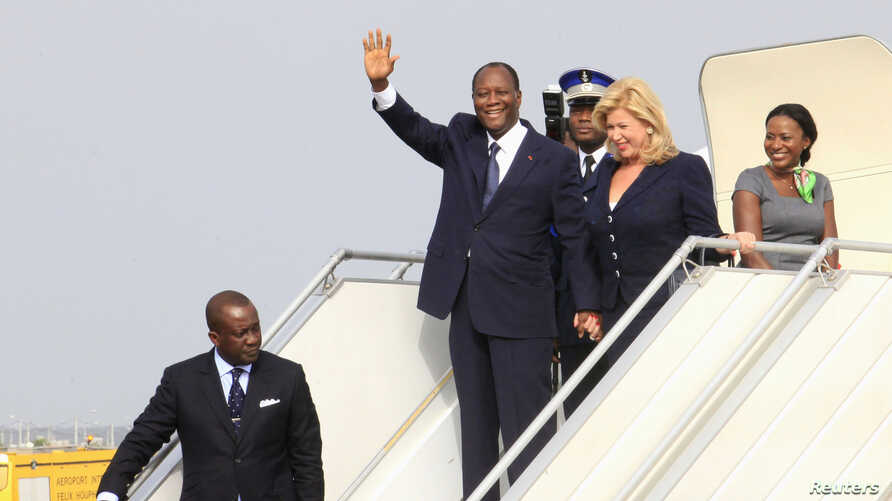 Ivory Coast's President Alassane Ouattara (L) waves next to wife Dominique (R) as they arrive at Felix Houphouet-Boigny international airport in Abidjan March 2, 2014.