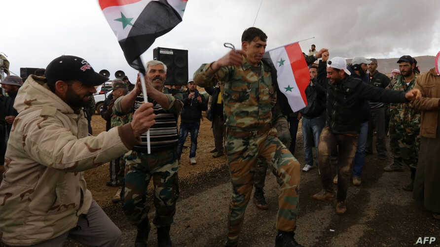 Syrian volunteers and relatives wave the national flag and portraits of President Bashar al-Assad as they celebrate at the end of paramilitary training conducted by the Syrian army in al-Qtaifeh, near Damascus, Feb. 22, 2016.