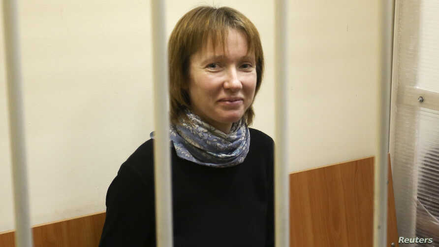 "Yekaterina Zaspa, the""Arctic Sunrise"" ship doctor and one of the 30 people who were arrested over a Greenpeace protest at the Prirazlomnaya oil rig, looks out from a defendants' cage as she attends a court session in St. Petersburg, Nov. 18, 2013."