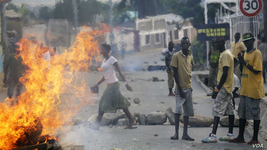 Protester stand by a burning barricade in the Musaga neighborhood of Bujumbura, Burundi, Thursday May 21, 2015. Protests continue against the  President's decision to seek a third term.  (AP Photo/Jerome Delay)