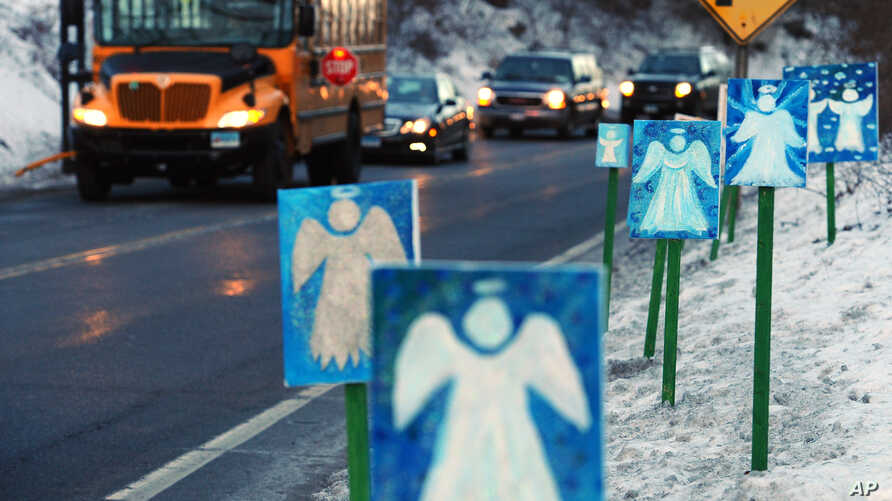 A bus traveling from Newtown, Connecticut, to Monroe stops in front of 26 angels along the roadside on the first day of classes for Sandy Hook Elementary School students since the December 14 shooting.