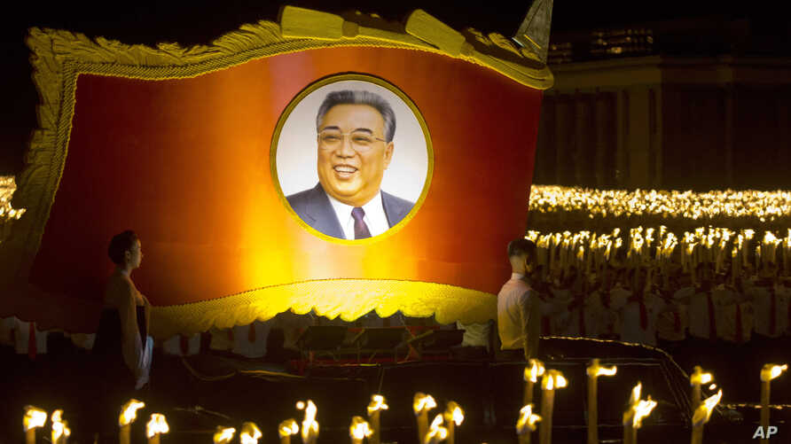A float with a portrait of late North Korean leader Kim Il Sung passes by North Korean students taking part in a torch light march held in conjunction with the 70th anniversary of North Korea's founding day celebrations in Pyongyang, North Korea, Sep