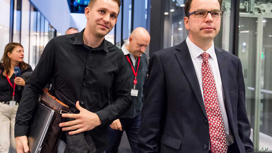 Max Schrems, left, and his lawyer Herwig Hofmann, right, walk in the hallway after a ruling at the European Court of Justice in Luxembourg on Tuesday, Oct. 6, 2015.