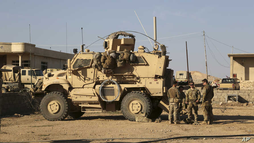 U.S. Army soldiers stand outside their armored vehicle on a joint base with Iraqi army south of Mosul, Iraq, Feb. 23, 2017.