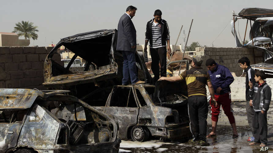 People inspect their destroyed cars at the scene of a car bomb attack in Ameen neighborhood in eastern Baghdad, Iraq, February 17, 2013.