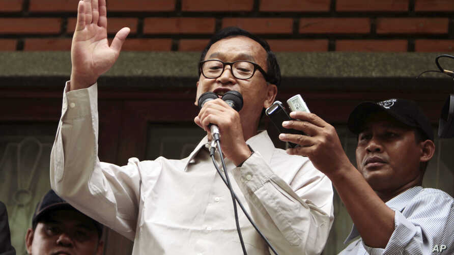 President of National Rescue Party Sam Rainsy, center, gives a speech during a public forum on the topic of the election of July 28, at their party's office in Phnom Penh, Cambodia, July 31, 2013.