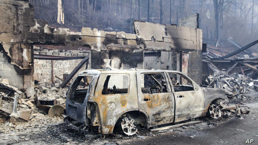 A scorched vehicle sits next to a burned-out building in Gatlinburg, Tennessee, Nov. 29, 2016.