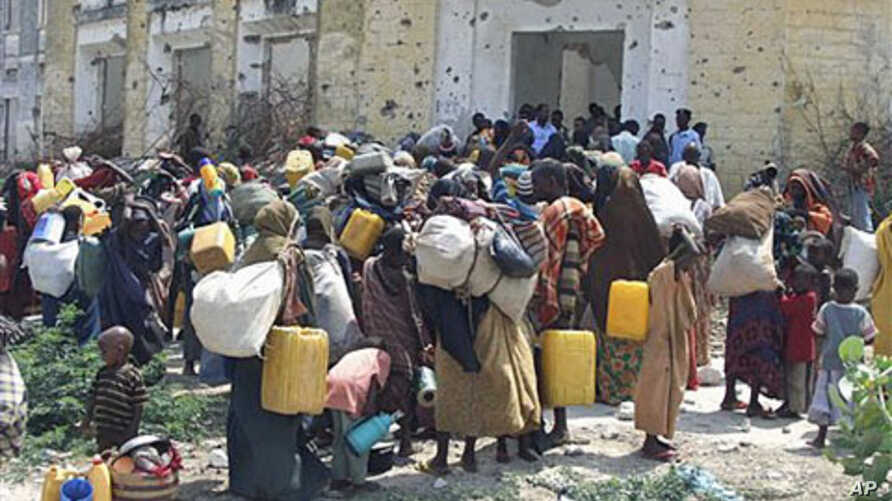 Somalis carrying their belongings wait outside an internally displaced camp in Mogadishu, Somalia, after they fleeing from southern Somalia due to lack of food and water, July 5, 2011