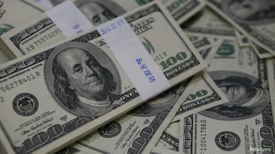 U.S. one-hundred dollar bills are seen in this photo illustration at a bank in Seoul August 2, 2013. Picture taken August 2, 2013. South Korea's foreign reserves jumped to a record high in July, the central bank said on August 5, 2013, appearing to s