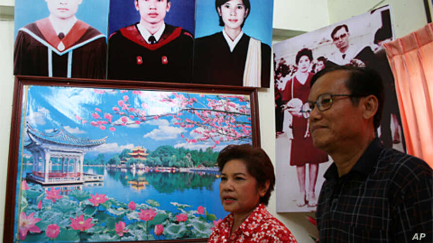 Middle class red shirt supporters Uraiwan Suwannasang, left, and Teerapan Suwannasang, in front of photos of their children at home in Ban Pheu, 17 May 2010