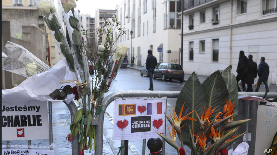 Flowers are attached to security fences outside Charlie Hebdo headquarters in Paris, France, Wednesday, Jan. 14, 2015, one week after the attack on the newspaper. France ordered prosecutors around the country to crack down on hate speech, anti-Semiti
