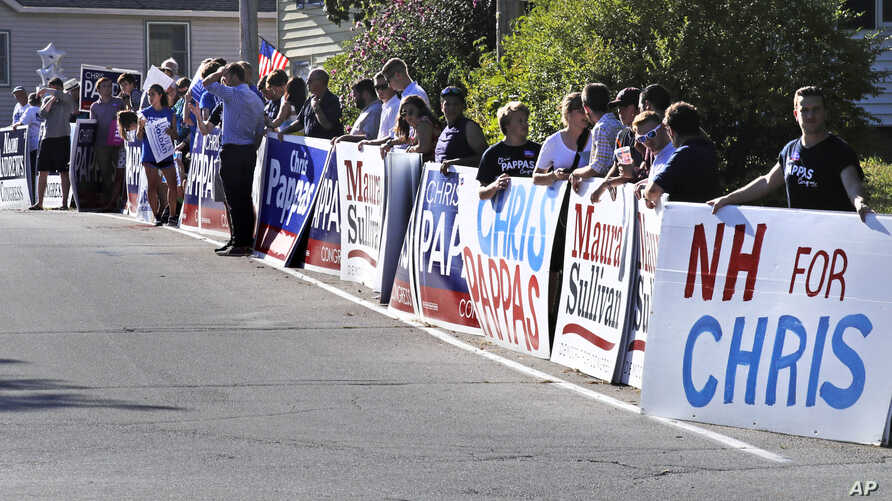 FILE - Democratic campaign supporters line the road leading to the New Hampshire Institute of Politics at St. Anselm College prior to a debate for New Hampshire's 1st Congressional District in Manchester, N.H., Sept. 5, 2018.