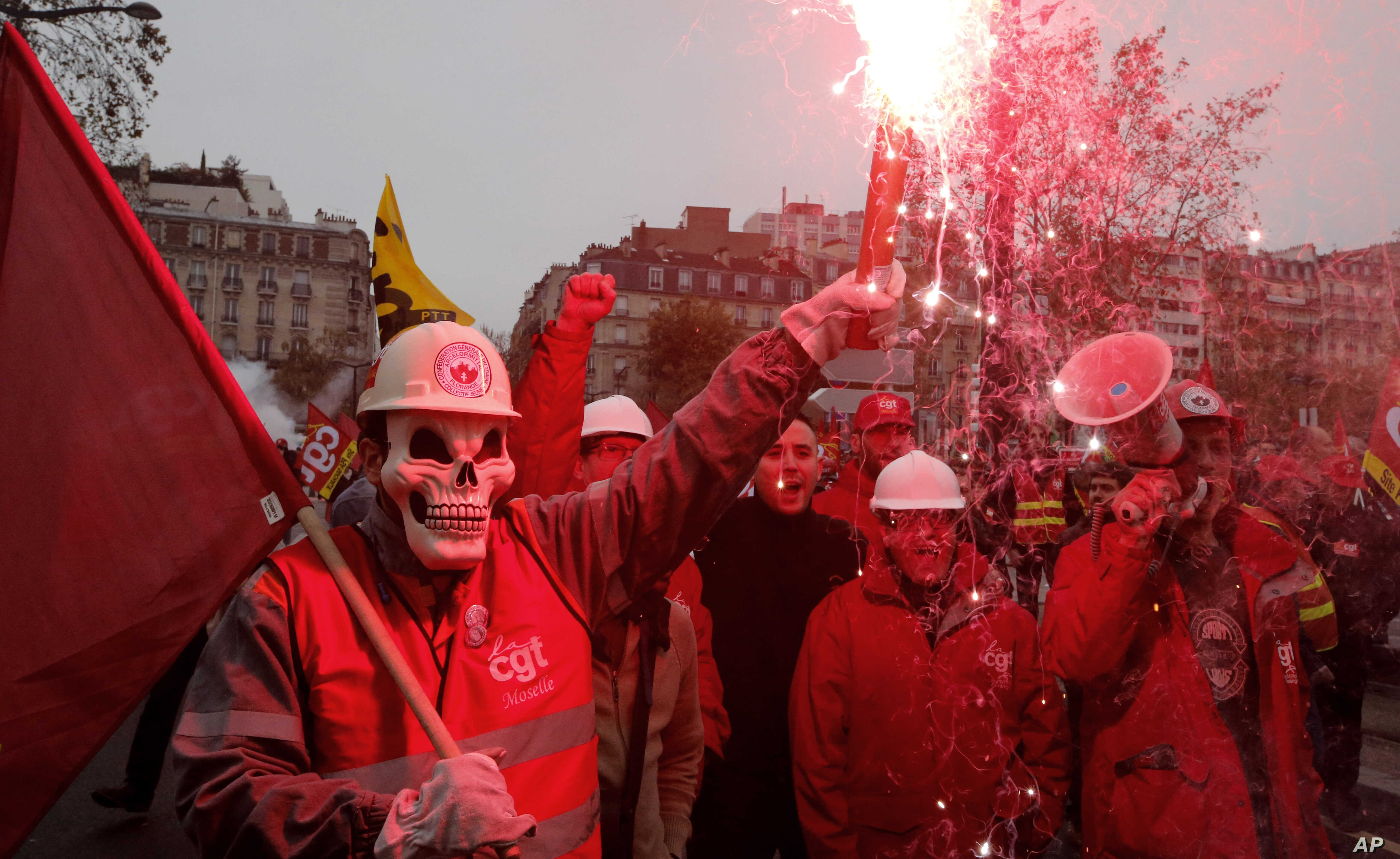 Union members hold safety flares during a demonstration in front of the entrance of the Paris auto show in Paris, Tuesday, Oct. 9, 2012.