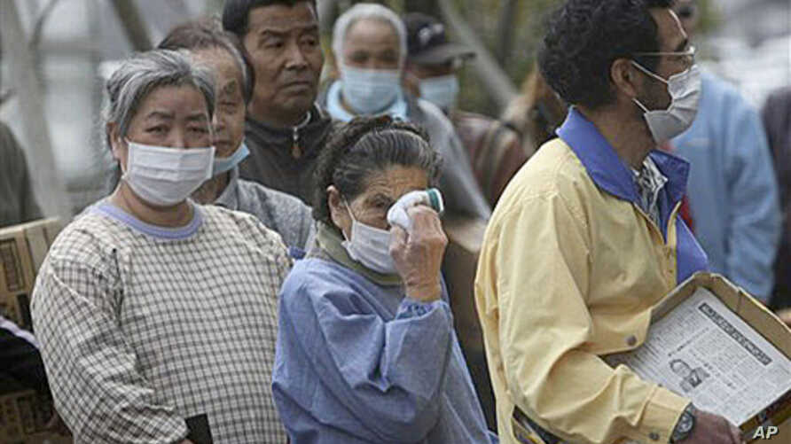 An elder woman wipes her eyes in long lines for food at an evacuation shelter in Koriyama, Fukushima prefecture, Japan, April 2, 2011