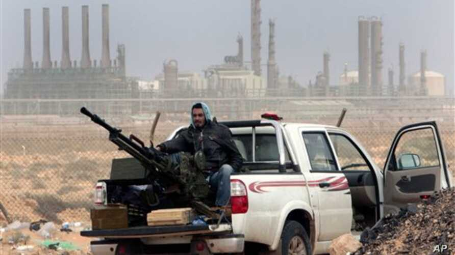 FILE - In this March 5, 2011 file photo, an anti-government rebel sits with an anti-aircraft weapon in front an oil refinery, after the capture of the oil town of Ras Lanouf, eastern Libya. The official Libyan news agency said Sunday, April 6, 2014 t