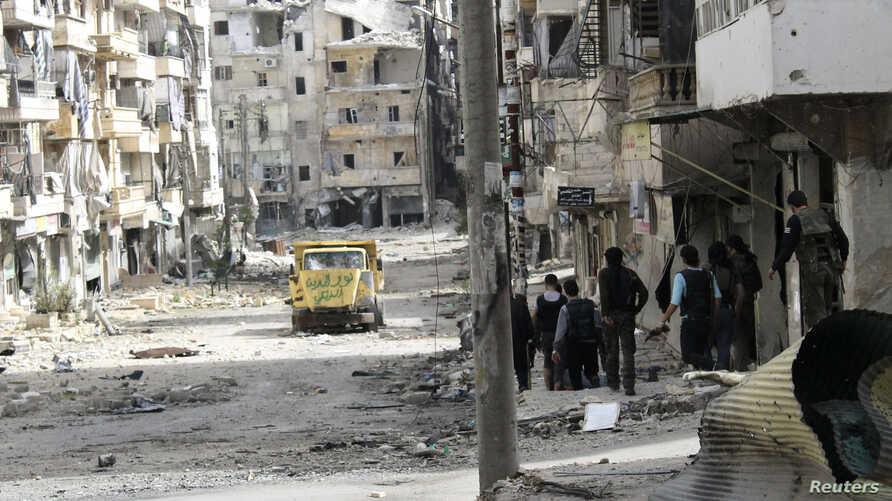 Free Syrian Army fighters walk along a street piled with damaged building as they head toward the frontline in Aleppo's Salaheddine district, April 8, 2013.