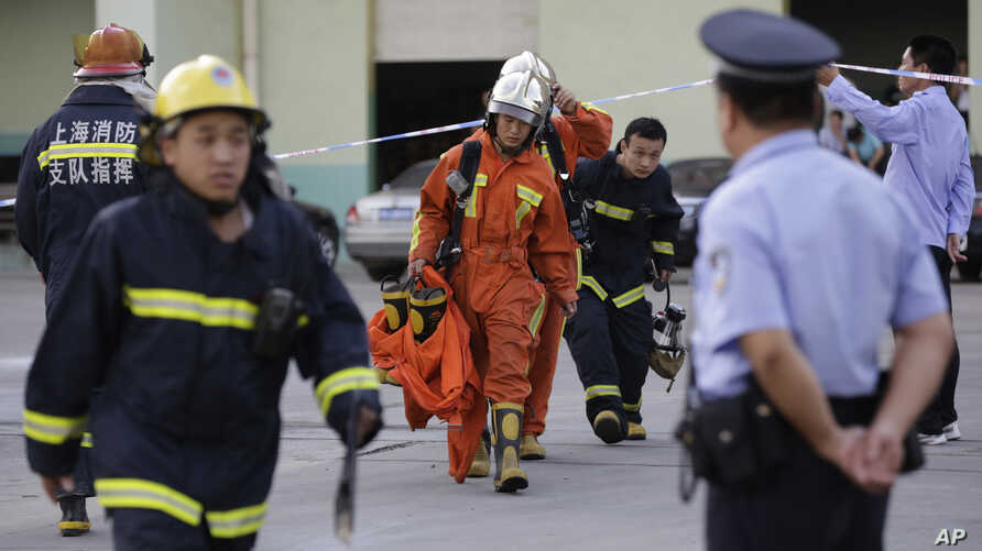 Firefighters walk out from the main gate of Weng's Cold Storage Industrial Co. Ltd. at the outskirts of Shanghai, China, Aug. 31, 2013.