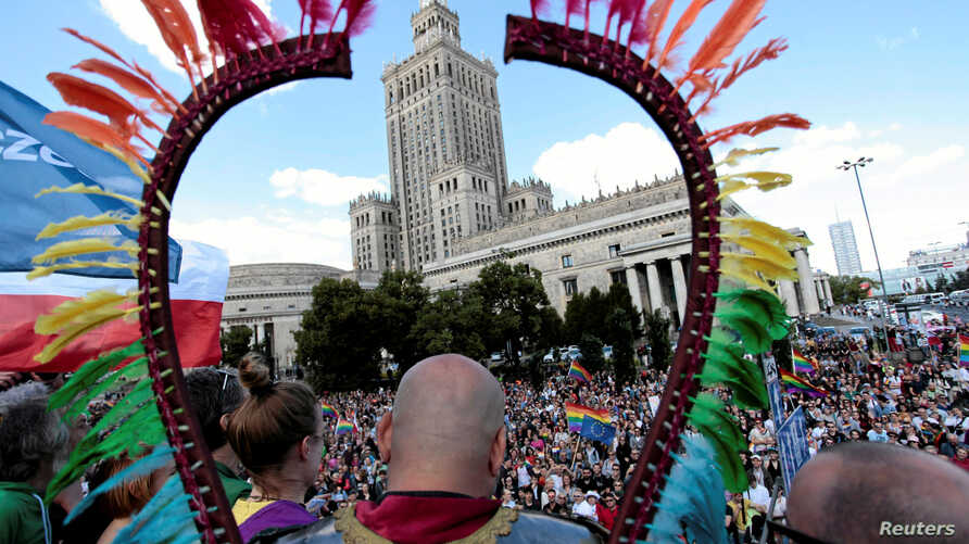FILE - People take part in the annual Equality Parade in front of the Palace of Culture and Science in Warsaw, Poland, June 11, 2016.