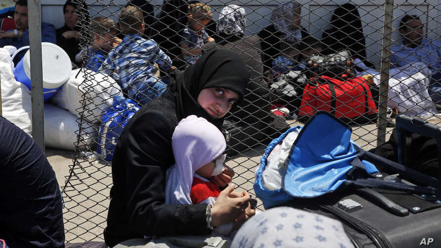 FILE - A Syrian woman and child living in Turkey wait to cross into Syria at the Oncupinar border crossing, near the town of Kilis, Turkey, June 13, 2017.