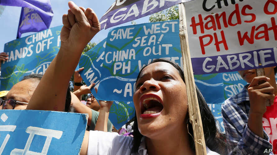 Protesters shout slogans during a rally outside of the Chinese Consulate hours before the Hague-based UN international arbitration tribunal is to announce its ruling on the South China Sea, July 12, 2016, in Makati city, east of Manila, Philippines.