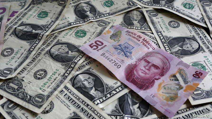 FILE - A picture illustration shows Mexican pesos and U.S. dollars banknotes in Mexico City.