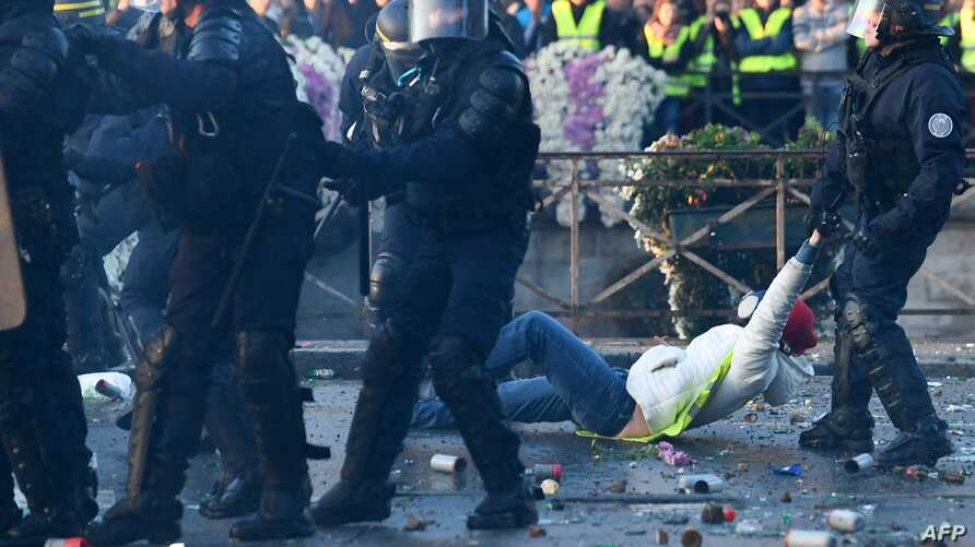 """A policeman evacuates a demonstrator in Quimper, western France, during a day of nationwide protest called """"yellow vest"""" (Gilets Jaunes in French) movement to protest against high fuel prices, Nov. 17, 2018."""