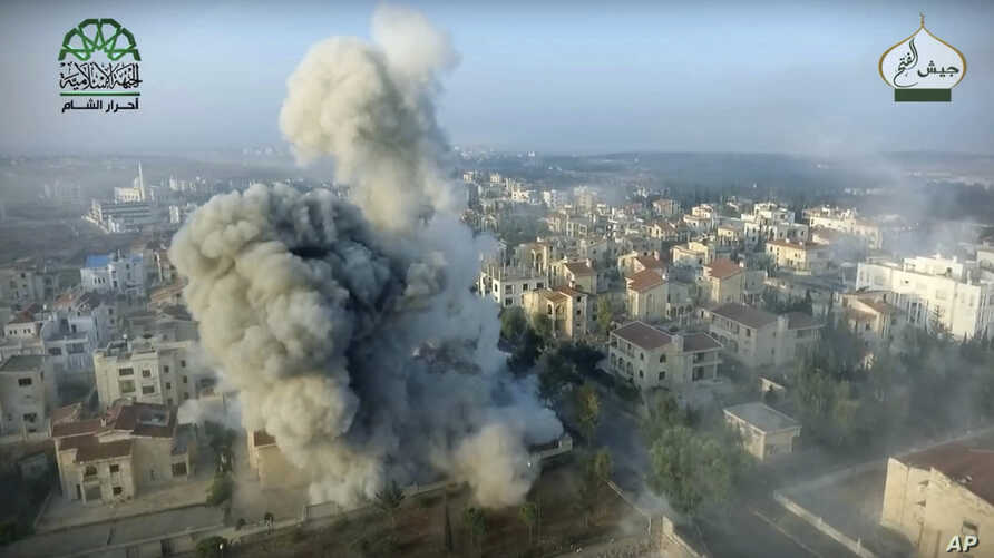This still image taken from drone footage, posted online by the communications arm of Ahrar al-Sham militant group, purports to show a blast on the ground, apparently the result of an airstrike, in a Syrian-government controlled neighborhood of Alep