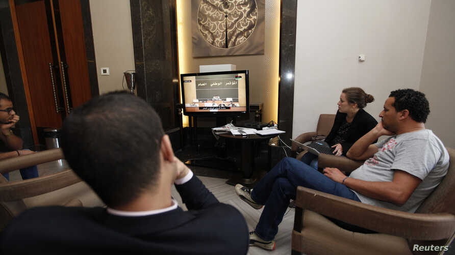 Reporters watch a live feed of Libyan members of parliament meeting to decide on the new prime minister at the parliament in Tripoli, May 4, 2014.
