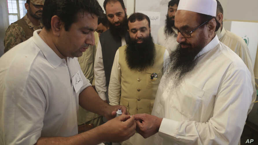 An election officer marks a thumb of Hafiz Saeed, right, head of the Pakistani religious party Jamaat-ud-Dawa, at polling station in Lahore, Pakistan, July 25, 2018.