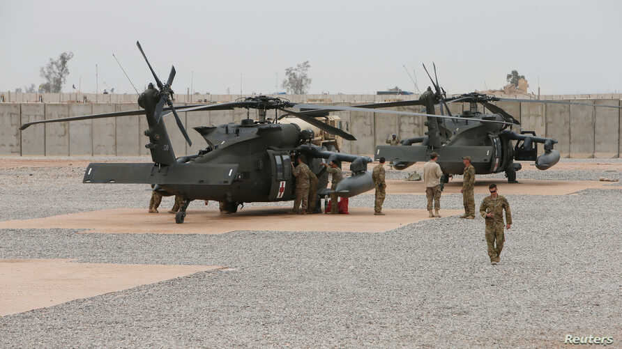 FILE - U.S. Army soldiers stand next to helicopters at Qayyarah West Airfield, Iraq, March 1, 2017. Seven U.S. service members were killed Thursday when their helicopter went down near the town of Al Qaim in Iraq's Anbar province.