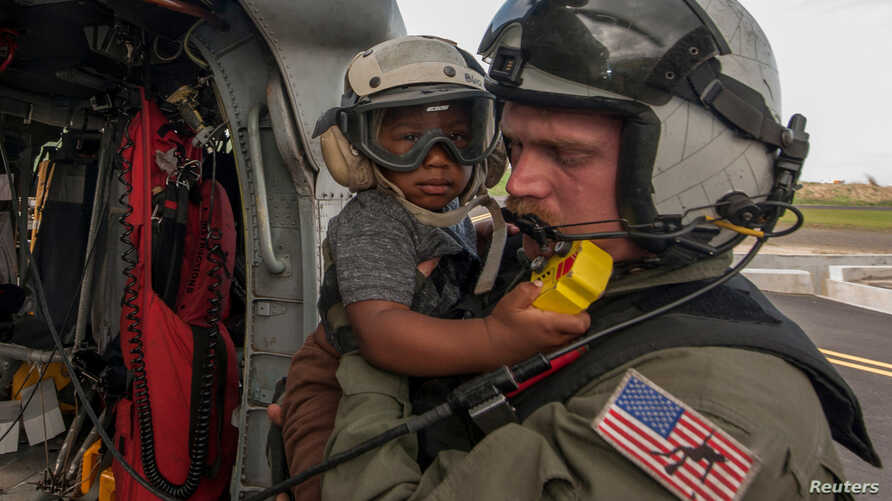 Naval Aircrewman 2nd Class Brandon Larnard, assigned to Helicopter Sea Combat Squadron, carries an evacuee off an MH-60S Sea Hawk helicopter following the landfall of Hurricane Maria on the island of Dominica, Sept. 27, 2017.