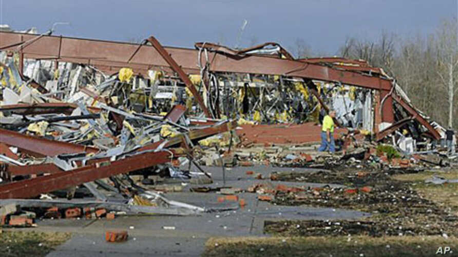 An employee of Henryville High School in Henryville, Indiana, examines the remains of the building following severe storms and tornadoes, March 2, 2012.