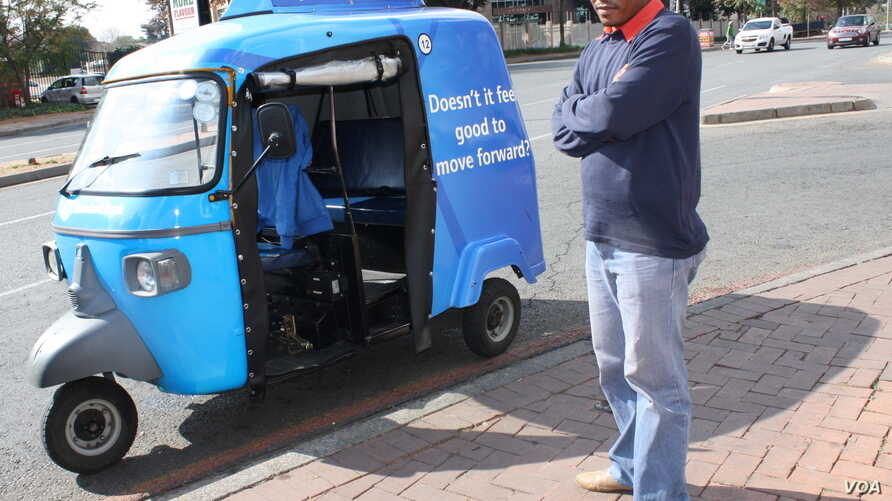 """""""People call our tuk tuks 'toy cars,'"""" says Johannesburg driver Alan Bangi as he waits for a fare at a Sandton intersection. (Photo by Darren Taylor)"""