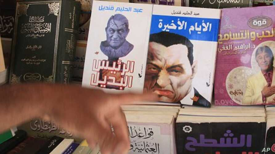 An Egyptian displays books showing cartoons on the covers of former Egyptian President Hosni Mubarak in Cairo, Egypt, May 23, 2011