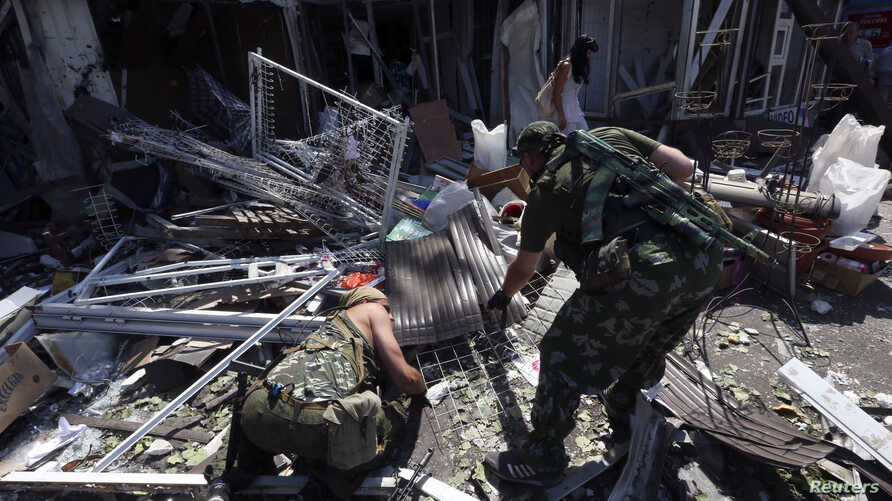 Armed pro-Russian separatists inspect wreckage near a damaged building following what locals say was a recent airstrike by Ukrainian forces in Donetsk, Aug. 6, 2014.