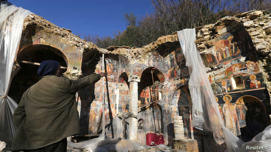A man points out a damaged fresco in The Orthodox Church of Saint Athanasios in Leshnica, Saranda, Albania, Jan. 25, 2018.