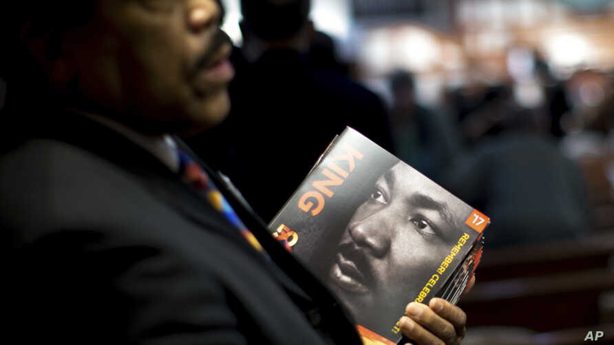 James R. Johnson hands out programs before the Rev. Martin Luther King Jr. holiday commemorative service at Ebenezer Baptist Church, Jan. 16, 2017, in Atlanta.