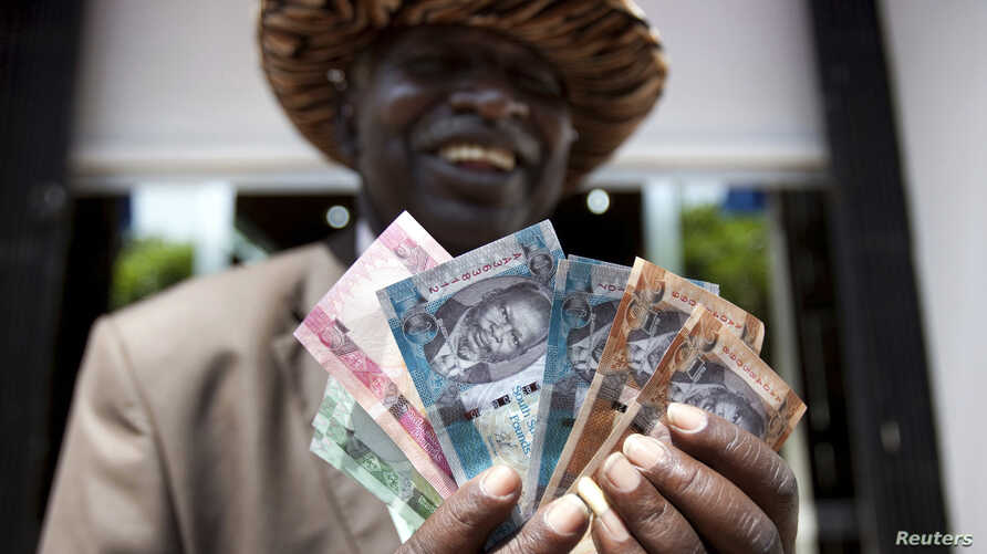 A man from South Sudan displays new currency notes outside the Central Bank of South Sudan in Juba, July 18, 2011.