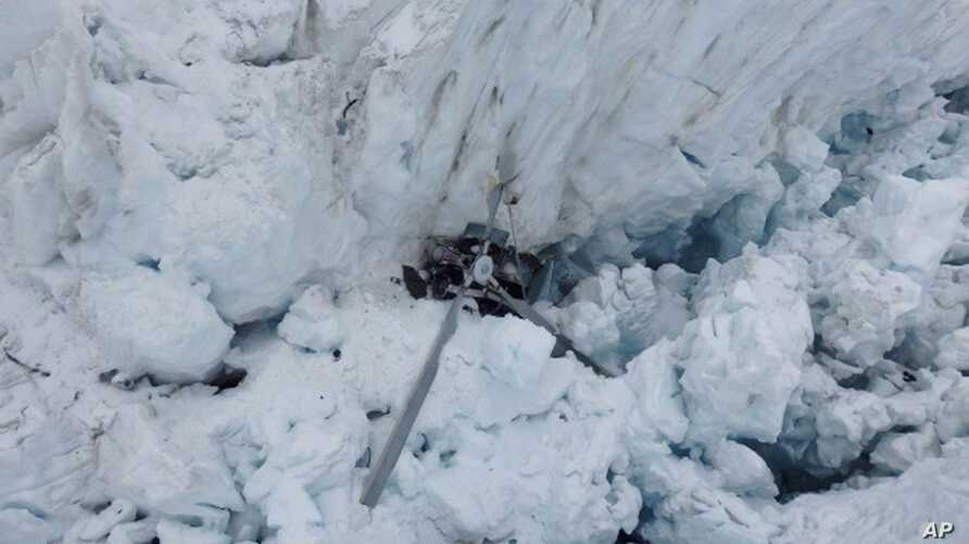 The wreckage of a helicopter carrying tourists is seen crashed in a crevasse on Fox Glacier, a scenic glacier in South Island, New Zealand, Nov. 21, 2015. All seven people, one pilot and six tourists, aboard the helicopter are believed to have been k