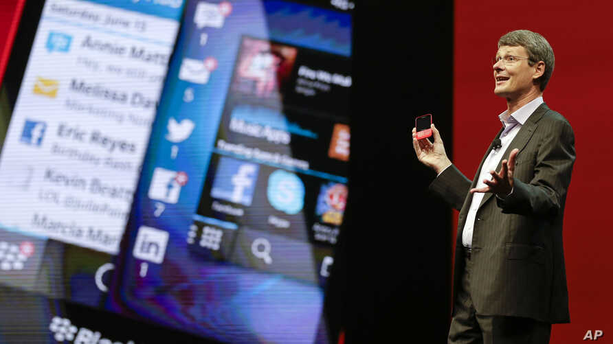 Thorsten Heins, president and CEO at BlackBerry holds up the new BlackBerry 10 mobile device at a conference,  May 14, 2013, in Orlando, Florida.