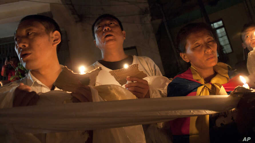 Tibetan exiles hold ceremonial scarves tied together as they participate in a candlelit vigil after reports of another self-immolation in Tibet, in Dharmsala, India, Oct. 5, 2012.