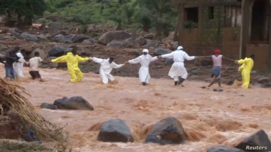 People wearing protective suits hold hands as they cross a river after a mudslide in the mountain town of Regent, Sierra Leone, Aug. 15, 2017, in this still image taken from a video
