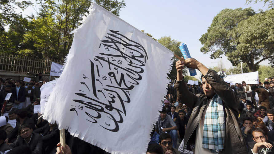 FILE - An Afghan student waves a white Taliban flag at a rally in Kabul, Afghanistan, Oct. 25, 2014.
