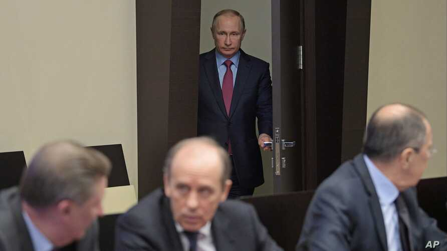 FILE - Federal Security Service (FSB) Chief Alexander Bortnikov (front, center) is seen at a Security Council meeting in the Novo-Ogaryovo residence outside Moscow, Russia, April 13, 2017, with Russian President Vladimir Putin entering in the backgro