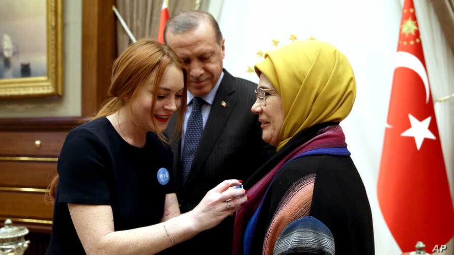 """FILE - U.S. actress Lindsay Lohan, left, places a badge bearing a quote from Turkey's President Recep Tayyip Erdogan, center, reading """"World is bigger than five,"""" referring to the UN Security Council's five permanent members."""