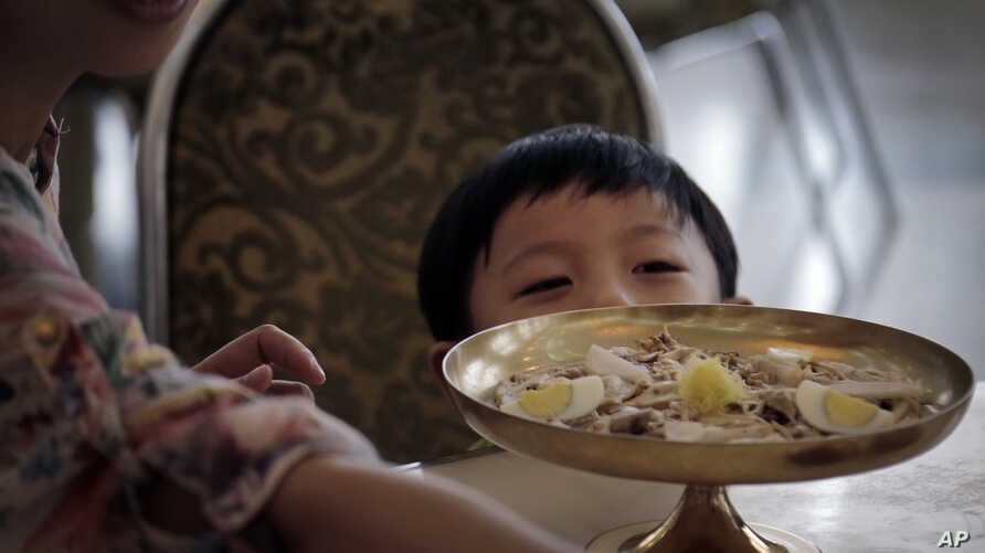 FILE - A young North Korean boy peeps over his serving of noodles at a restaurant in Pyongyang, Sept. 1, 2014.
